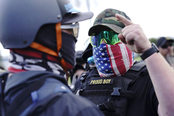 """FILE - In this Sept. 26, 2020 file photo, a right-wing demonstrator gestures toward a counter protester as members of the Proud Boys and other right-wing demonstrators rally in Portland, Ore. President Donald Trump didn't condemn white supremacist groups and their role in violence in some American cities this summer. Instead, he said the violence is a """"left-wing"""" problem and he told one far-right extremist group to """"stand back and stand by."""" His comments Tuesday night were in response to debate moderator Chris Wallace asking if he would condemn white supremacists and militia groups. Trump's exchange with Democrat Joe Biden left the extremist group Proud Boys celebrating what some of its members saw as tacit approval. (AP Photo/John Locher, File)"""