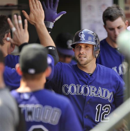 Colorado Rockies' Andrew Brown celebrates with teammates in the dugout after hitting a solo home run against the Chicago Cubs in the sixth inning of a baseball game in Chicago, Saturday, Aug. 25, 2012. Colorado won 4-3. (AP Photo/Paul Beaty)