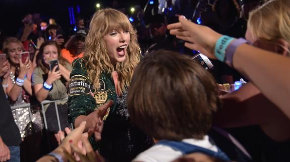 Taylor Swift calls herself a 'third wheel' as two fans get engaged at meet and greet