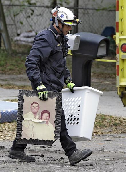 A Hillsborough County, Fla., firefighter removes salvaged items, including a family photo, from the home where a sinkhole swallowed Jeffrey Bush, late Thursday in Seffner, Fla., on Sunday, March 3, 2013. Crews are set to begin the demolition of the home on Sunday, after search personnel failed to find Bush. (AP Photo/Chris O'Meara)
