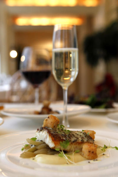 In this Dec. 7, 2012 photo, local snapper with crawfish sausage, creamed potato, fennel, caviar butter, by executive chef Kristin Butterworth, is seen with wine pairings, at the Grill Room of the Windsor Court Hotel in New Orleans. Roughly 50 restaurants in New Orleans are reviving an old Creole custom called reveillon, which stems from the old French tradition of eating a lavish meal after midnight Mass on Christmas Eve. (AP Photo/Gerald Herbert)