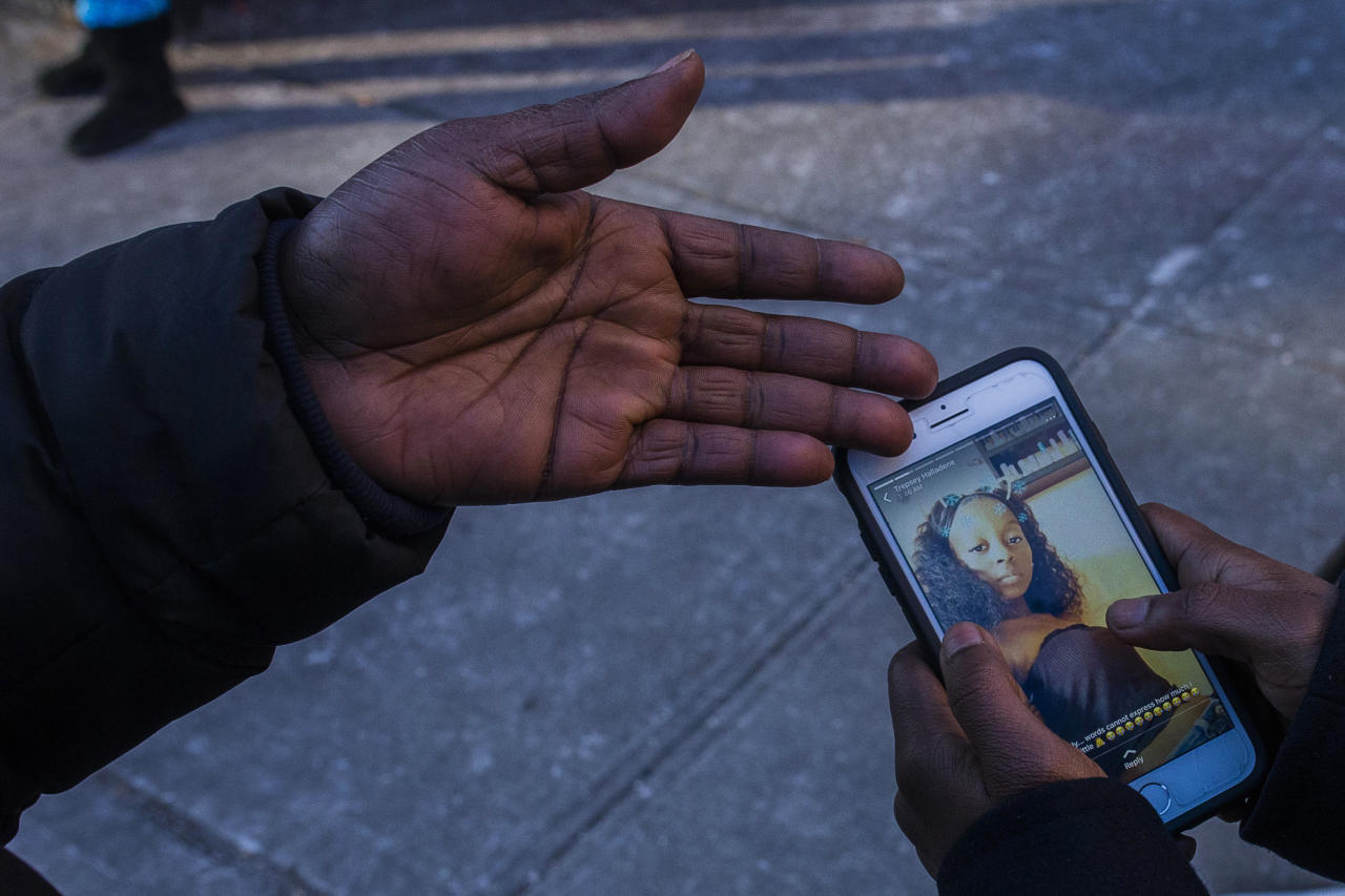 <p>Sasha Answer, resident of an apartment building where there was a Thursday fire, talks to a friend as he displays a picture published in social media of Shawtay Young, who was one of the victims who died in the fire, in the Bronx, New York, Friday, Dec. 29, 2017. (Photo: Andres Kudacki/AP) </p>