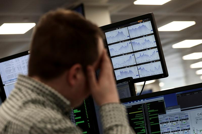 A trader looks at financial information on computer screens on the IG Index the trading floor in London, Britain February 6, 2018. REUTERS/Simon Dawson