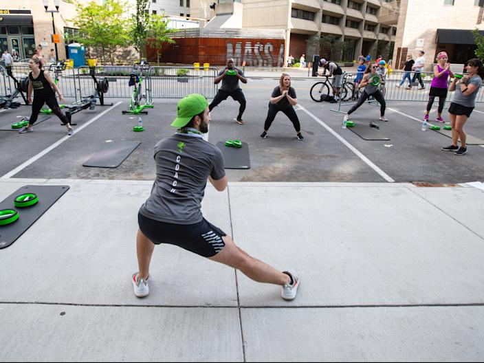 Jacob Morden leads a fitness class on a closed street in downtown Indianapolis, Friday, May 22, 2020.