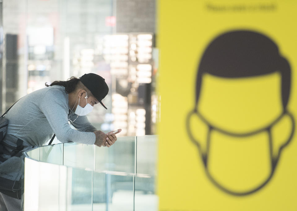A man wears a face mask as he browses on his phone in a shopping mall in Montreal, Sunday, August 2, 2020, as the COVID-19 pandemic continues in Canada and around the world. The Quebec government has made the wearing of masks and face coverings mandatory in all public spaces as of July 18 and will increase the number of people allowed to gather indoors and outdoors to 250 people as of August 3. THE CANADIAN PRESS/Graham Hughes