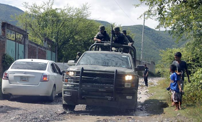 Mexican marines guard the site where a number of bodies were found in unmarked graves on the outskirts of Iguala, Guerrero state, on October 4,2014, the southern Mexico town where 43 students disappeared after a deadly police shooting last week (AFP Photo/Jesus Guerrero)