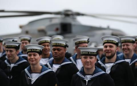 Members of the crew of HMS Queen Elizabeth, the UK's newest aircraft carrier, muster on the deck ahead of the ship's arrival in Portsmouth - Credit: Andrew Matthews/PA