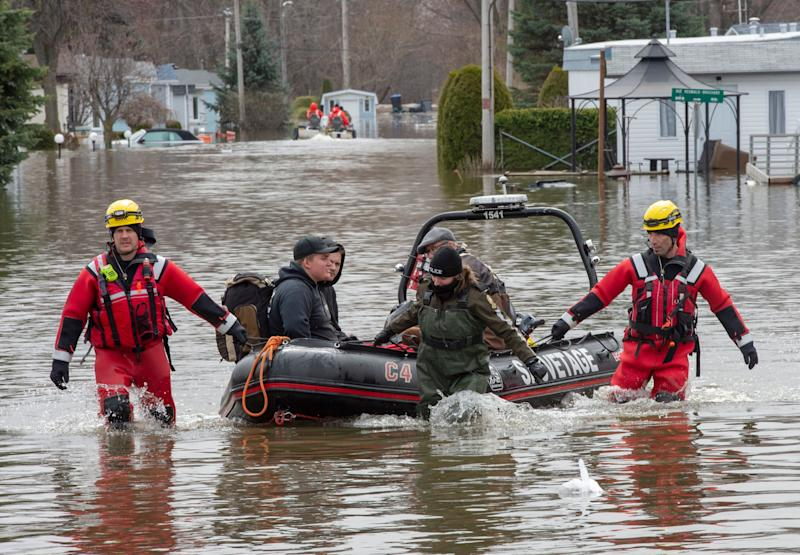 Rescue workers help evacuees retrieve some belongings from flooding from the Lake of Two Mountains, Wednesday, May 1, 2019, in Sainte-Marthe-sur-le-Lac, Quebec, Canada. (Ryan Remiorz/The Canadian Press via AP)