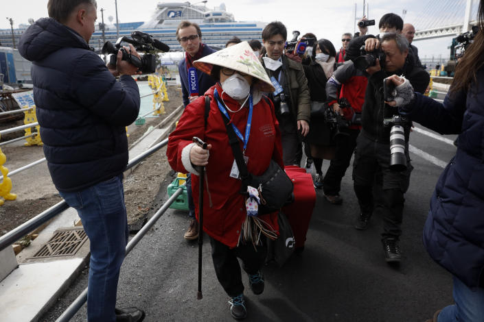 An unidentified passenger is surrounded by the media after she disembarked from the quarantined Diamond Princess cruise ship on Feb. 19, 2020, in Yokohama, Japan.
