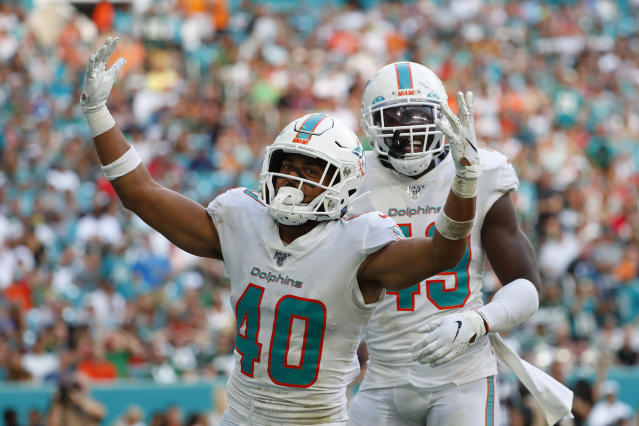 Miami Dolphins defensive back Nik Needham (40) celebrates with Miami Dolphins linebacker Sam Eguavoen (49) after he sacked New York Jets quarterback Sam Darnold during the second half of an NFL football game, Sunday, Nov. 3, 2019, in Miami Gardens, Fla. (AP Photo/Wilfredo Lee)