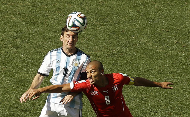 Argentina's Lionel Messi, left, goes for a header beside Switzerland's Goekhan Inler during the World Cup round of 16 soccer match between Argentina and Switzerland at the Itaquerao Stadium in Sao Paulo, Brazil, Tuesday, July 1, 2014. (AP Photo/Thanassis Stavrakis)