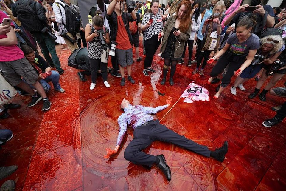 A member of Extinction Rebellion rolling around in fake blood in Paternoster Square, close to St Paul's Cathedral (Kirsty O'Connor/PA) (PA Wire)