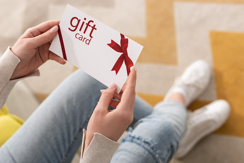 Cropped view of girl holding gift card with red bow