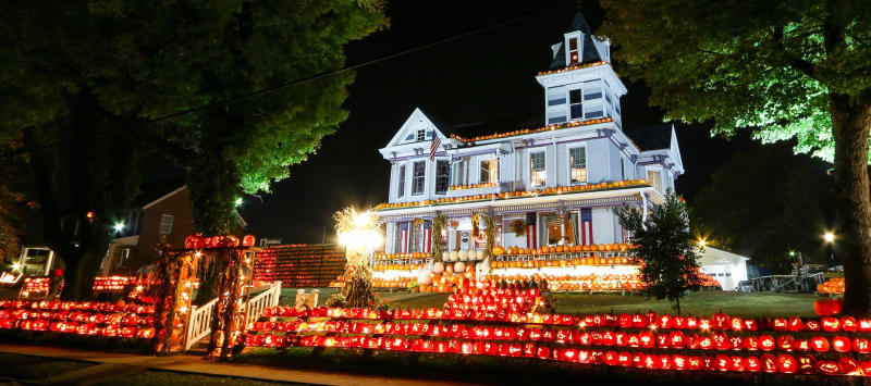 Exterior of white Victorian house with rows of carved pumpkins lined up in front yard