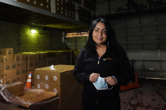 Gladys Vega, executive director of La Colaborativa, poses inside the nonprofit's food pantry warehouse in Chelsea, Mass., Feb. 10, 2021. Vega's organization has partnered with a community health center to launch a public vaccination site at its office on Broadway, the city's bustling main street. (AP Photo/Elise Amendola)