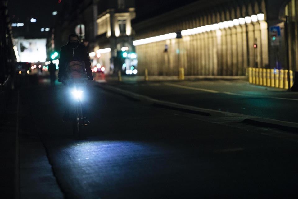 A man rides a bike on Rivoli street during curfew in Paris, Saturday, Oct. 17, 2020. French restaurants, cinemas and theaters are trying to figure out how to survive a new curfew aimed at stemming the flow of record new coronavirus infections. The monthlong curfew came into effect Friday at midnight, and France is deploying 12,000 extra police to enforce it. (AP Photo/Lewis Joly)