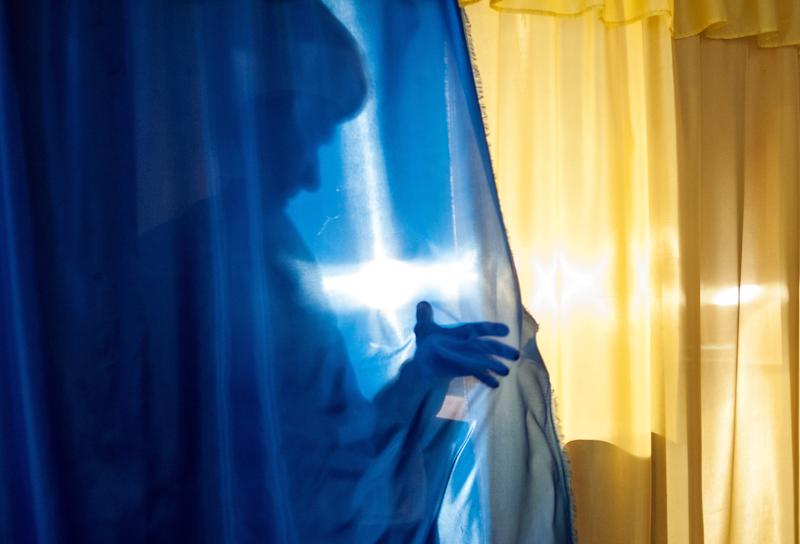 A local resident casts a shadow leaving a booth to cast her ballot at a polling station in Luhansk, Ukraine, on Sunday, May 11, 2014. Residents of two restive regions in eastern Ukraine cast ballots Sunday in referendums, which seek approval for declaring sovereign people's republics in the Donetsk and Luhansk regions. (AP Photo/Evgeniy Maloletka)