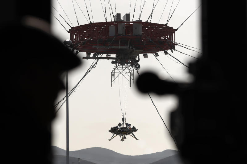 A journalist films a lander lifted during a test of hovering, obstacle avoidance and deceleration capabilities at a facility in Huailai in China's Hebei province, Thursday, Nov. 14, 2019. China has invited international observers to the test of its Mars lander as it pushes for inclusion in more global space projects. Thursday's test was conducted at a site outside Beijing simulating conditions on the Red Planet, where the pull of gravity is about one-third that of Earth. (AP Photo/Andy Wong)