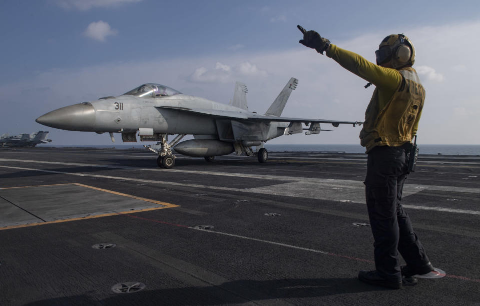 In this photo released by the U.S. Navy, Aviation Boatswain's Mate 3rd Class Marnell Maglasang, from La Puente, Calif., directs an F/A-18E Super Hornet on the flight deck of the aircraft carrier USS Nimitz in the Arabian Sea, Friday Nov. 27, 2020. The Nimitz returned to the Mideast in a move to support the drawdown of troops in Afghanistan and Iraq according to the Pentagon. However, the Nimitz's announced arrival came after the killing of an Iranian scientist who founded the Islamic Republic's military nuclear program in the early 2000s. (Mass Communication Specialist 3rd Class Cheyenne Geletka/U.S. Navy via AP)