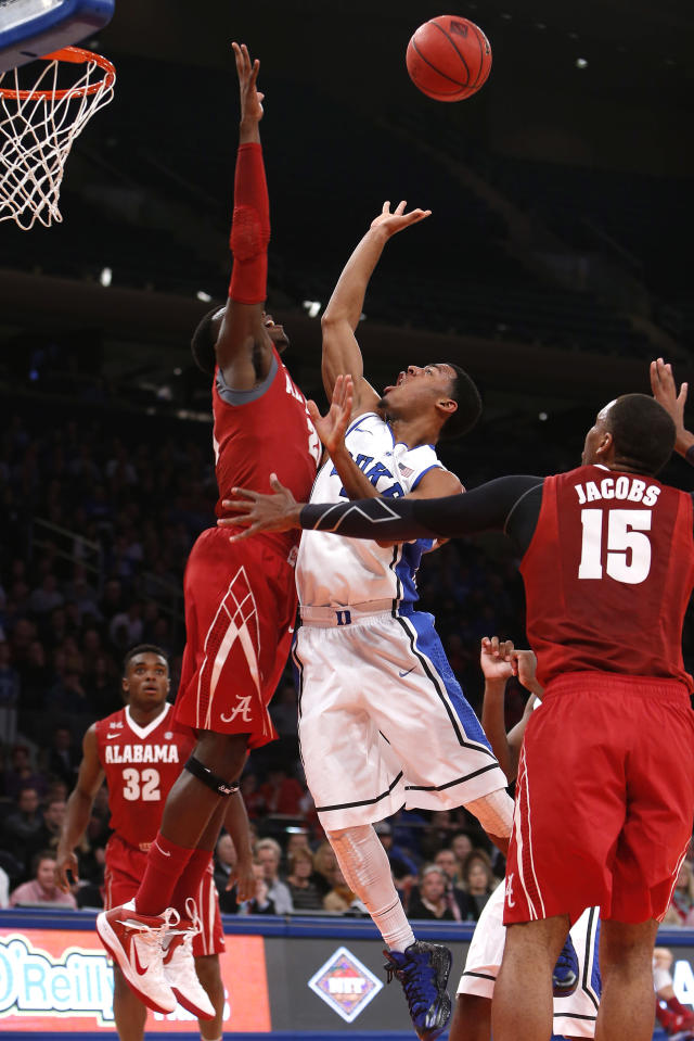 Duke's Quinn Cook, center, shoots against Alabama's Rodney Cooper, left, during the first half of an NCAA college basketball game in the semifinals of the NIT Season Tip-off tournament Wednesday, Nov. 27, 2013, in New York. (AP Photo/Jason DeCrow)