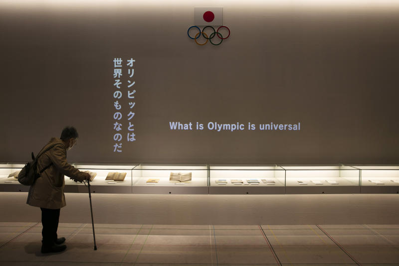 A woman looks at displays at the newly opened Tokyo Olympic Museum located near the New National Stadium, Sunday, Feb. 23, 2020, in Tokyo. (AP Photo/Jae C. Hong)