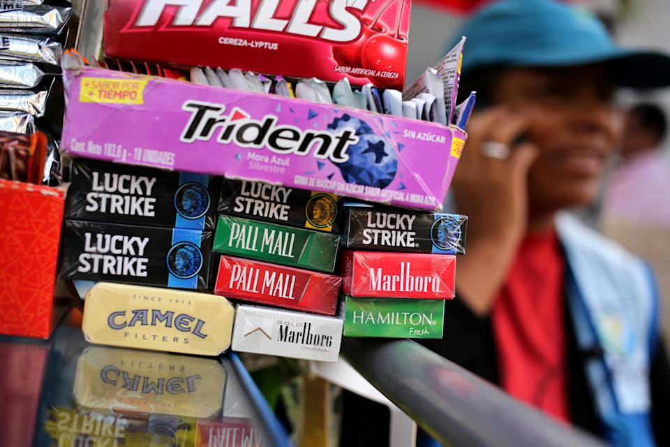 A woman sells cigarette packages of Lucky Strike, Marlboro, Pall Mall, Hamilton and Camel at a street in Lima, Peru. Photo: Mariana Bazo/Reuters
