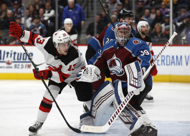 New Jersey Devils center Nico Hischier, left, looks around Colorado Avalanche goaltender Pavel Francouz for a pass in front of the net in the second period of an NHL hockey game Friday, Dec. 13, 2019, in Denver. (AP Photo/David Zalubowski)