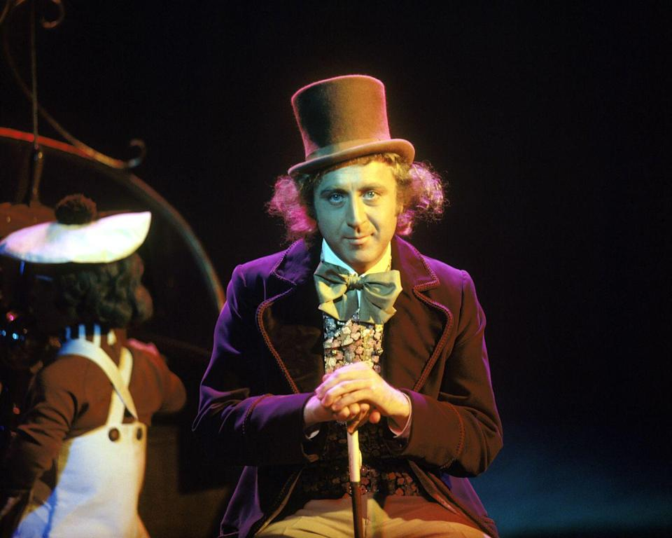 <p>Gene Wilder dons Willy Wonka's signature velvet plum jacket, bowtie, and top hat as he prepares to shoot a scene with the actors portraying Oompa Loompas.</p>