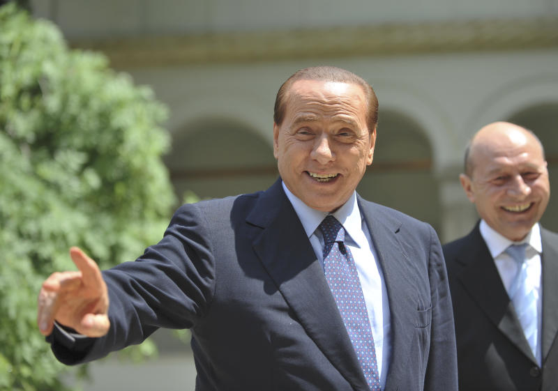 Italian Prime Minister Silvio Berlusconi, left, gestures while walking with Romanian President Traian Basescu, right, at the Cotroceni Presidential Palace in Bucharest, Tuesday, May 31, 2011. Berlusconi is on a two-day official visit to Romania. Berlusconi's defense lawyers fought to get his sensational under-age prostitution trial moved out of criminal courts on Tuesday as the Italian leader battled for his political future after suffering a withering defeat in local elections nationwide. (AP Photo/Octav Ganea)