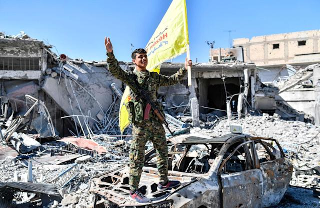 <p>A member of the Syrian Democratic Forces (SDF), which is backed by U.S. Special Forces troops, holds up the SDF flag at the Al-Naim square in Raqqa on Oct. 17, 2017. (Photo: Bulent Kilic/AFP/Getty Images) </p>