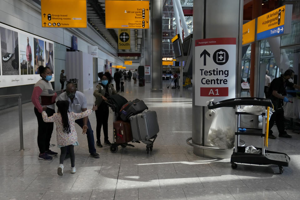 Passengers are greeted by a child as they arrive at Terminal 5 of Heathrow Airport in London, Monday, Aug. 2, 2021. Travelers fully vaccinated against coronavirus from the United States and much of Europe were able to enter Britain without quarantining starting today, a move welcomed by Britain's ailing travel industry. (AP Photo/Matt Dunham)
