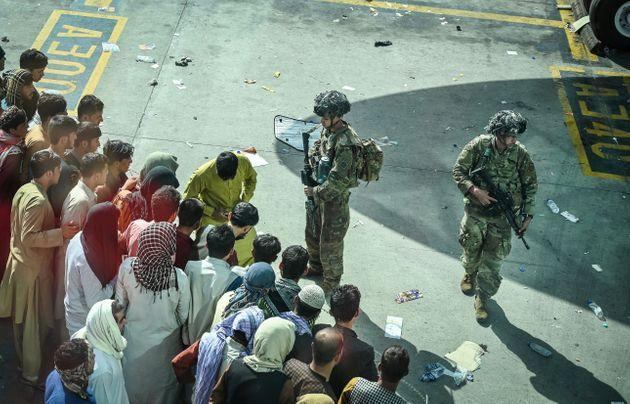 US soldiers stand guard as Afghan people wait at the Kabul airport in Kabul on August 16, 2021 (Photo: WAKIL KOHSAR via Getty Images)
