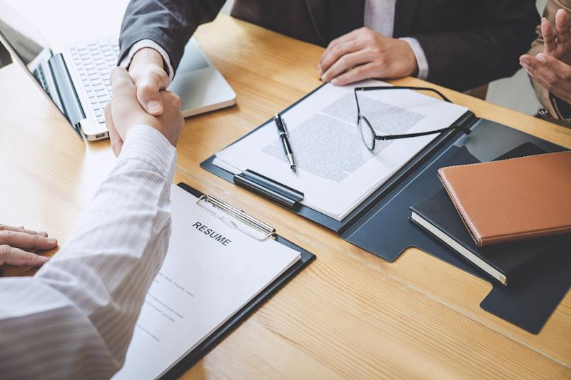 Midsection Of Employer Giving Handshake To Candidate In Office