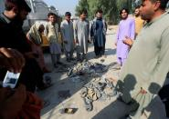 Afghan people stand over abandoned shoes of those who attended collecting tokens needed to apply for the Pakistan visa in Jalalabad