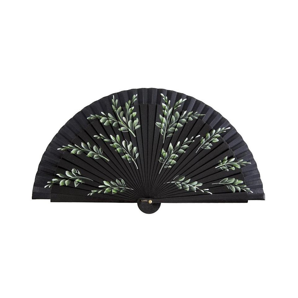 """Aside from looking chic (and being a totally unexpected gift), this hand-painted fan can be put to good use on sunny days when she's out and about. Think of it as her secret weapon for when AC units are nowhere to be found. $80, Fern Fans. <a href=""""https://www.fernfans.com/shop/small-floral-fan-in-black-leaves"""" rel=""""nofollow noopener"""" target=""""_blank"""" data-ylk=""""slk:Get it now!"""" class=""""link rapid-noclick-resp"""">Get it now!</a>"""