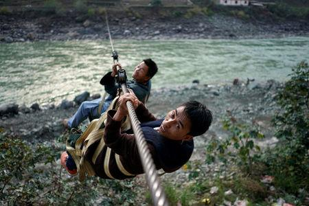 Villagers are seen crossing the river with a zipline in Lazimi village in Nujiang Lisu Autonomous Prefecture in Yunnan province, China, March 28, 2018. Picture taken March 28, 2018. REUTERS/Aly Song