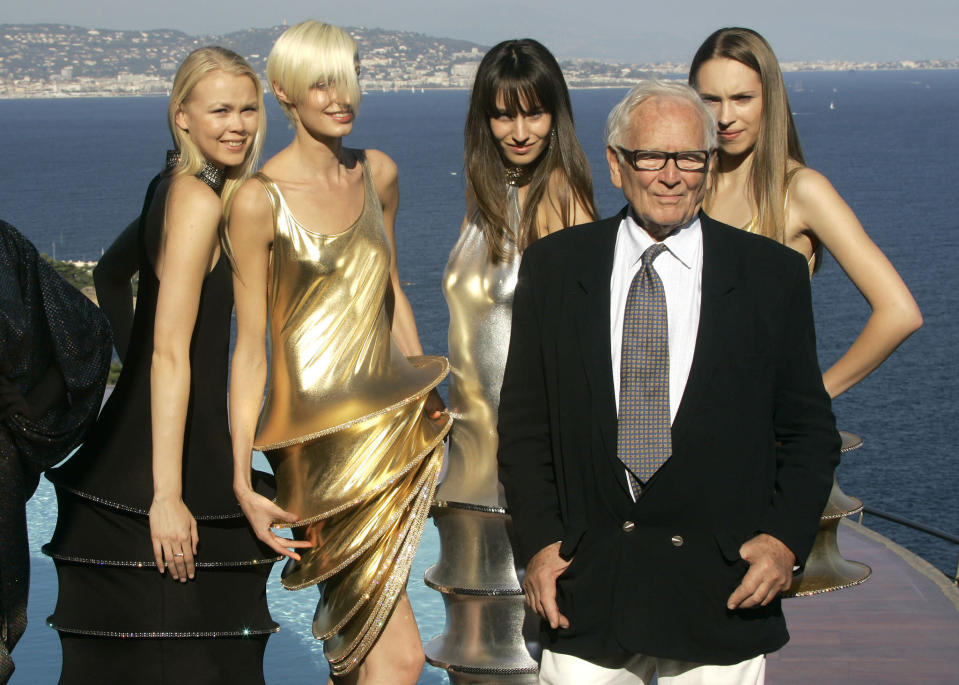 FILE - In this Oct.6, 2008 file photo, French fashion designer Pierre Cardin stands with models wearing his creations at his villa in Theoule sur Mer, southern France. France's Academy of Fine Arts says Pierre Cardin, the French designer whose Space Age style was among the iconic looks of 20th-century fashion, has died at 98. (AP Photo/Lionel Cironneau, File)
