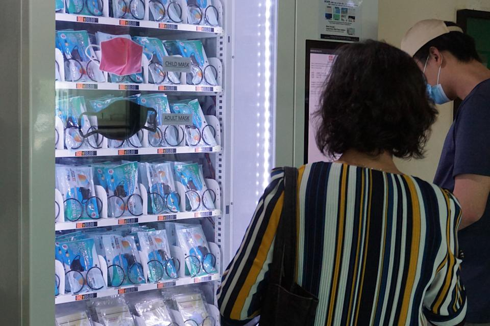Residents get free reusable face masks from a vending machine by scanning their identification card, set up by the government as part of the effort to halt the spread of the COVID-19 coronavirus, at a community centre in Singapore on May 28, 2020. (Photo by ROSLAN RAHMAN / AFP) (Photo by ROSLAN RAHMAN/AFP via Getty Images)