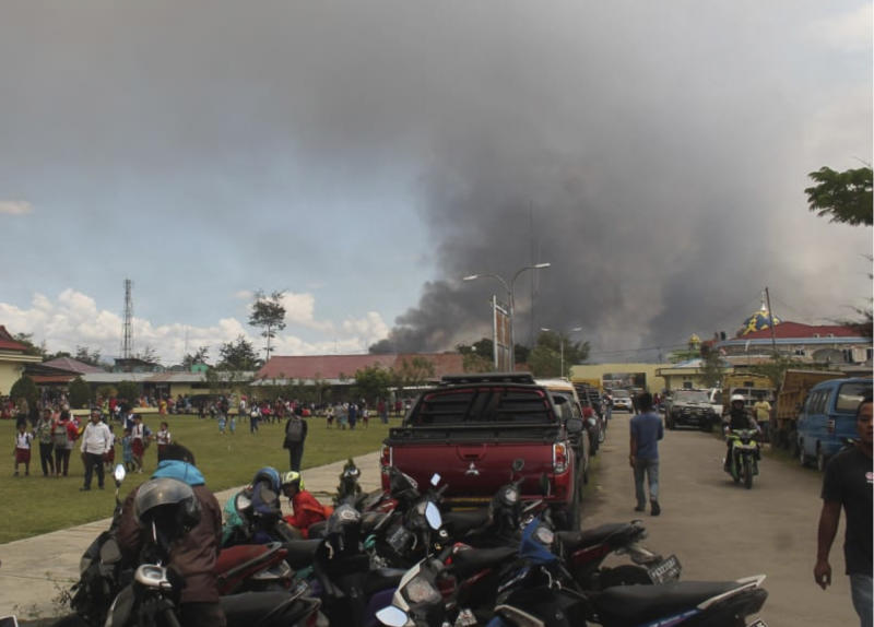 Smoke billows from burning building during protest in Wamena, Papua province, Indonesia, Monday, Sept. 23, 2019.  Hundreds of protesters in Indonesia's restive Papua province set fire to homes and other buildings Monday in a protest sparked by rumours that a teacher had insulted students. (AP Photo/George Yewun)