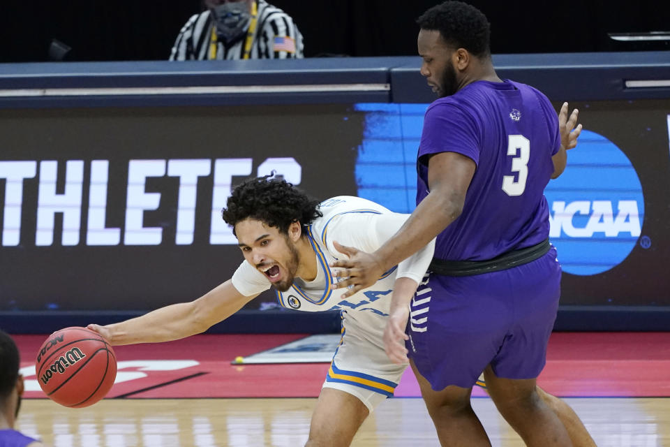 UCLA's Johnny Juzang, left, tries to get past Abilene Christian's Airion Simmons (3) during the first half of a college basketball game in the second round of the NCAA tournament at Bankers Life Fieldhouse in Indianapolis Monday, March 22, 2021. (AP Photo/Mark Humphrey)