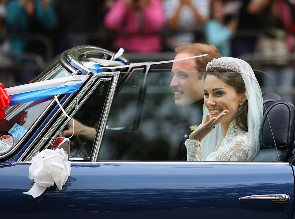 """<p>Prince William, Duke of Cambridge and Catherine, Duchess of Cambridge drive in a decorated vintage Aston Martin sports car in London, England <a href=""""https://www.townandcountrymag.com/the-scene/weddings/g20052313/kate-middleton-prince-william-royal-wedding-2011-photos/"""" rel=""""nofollow noopener"""" target=""""_blank"""" data-ylk=""""slk:on their wedding day"""" class=""""link rapid-noclick-resp"""">on their wedding day</a>. Middleton waves to the crowd, still dressed in her Sarah Burton for Alexander McQueen <a href=""""https://www.townandcountrymag.com/the-scene/weddings/a20517182/kate-middleton-wedding-dress/"""" rel=""""nofollow noopener"""" target=""""_blank"""" data-ylk=""""slk:wedding gown"""" class=""""link rapid-noclick-resp"""">wedding gown</a>.</p>"""