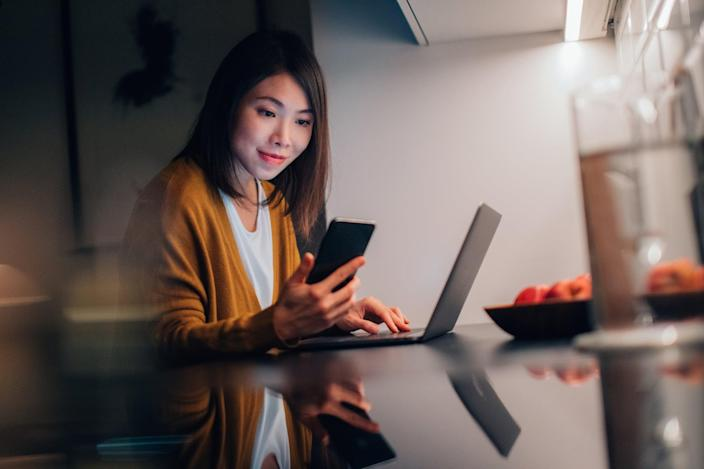 Beautiful young Asian woman looking at smartphone while working with laptop in the kitchen at home in the evening.