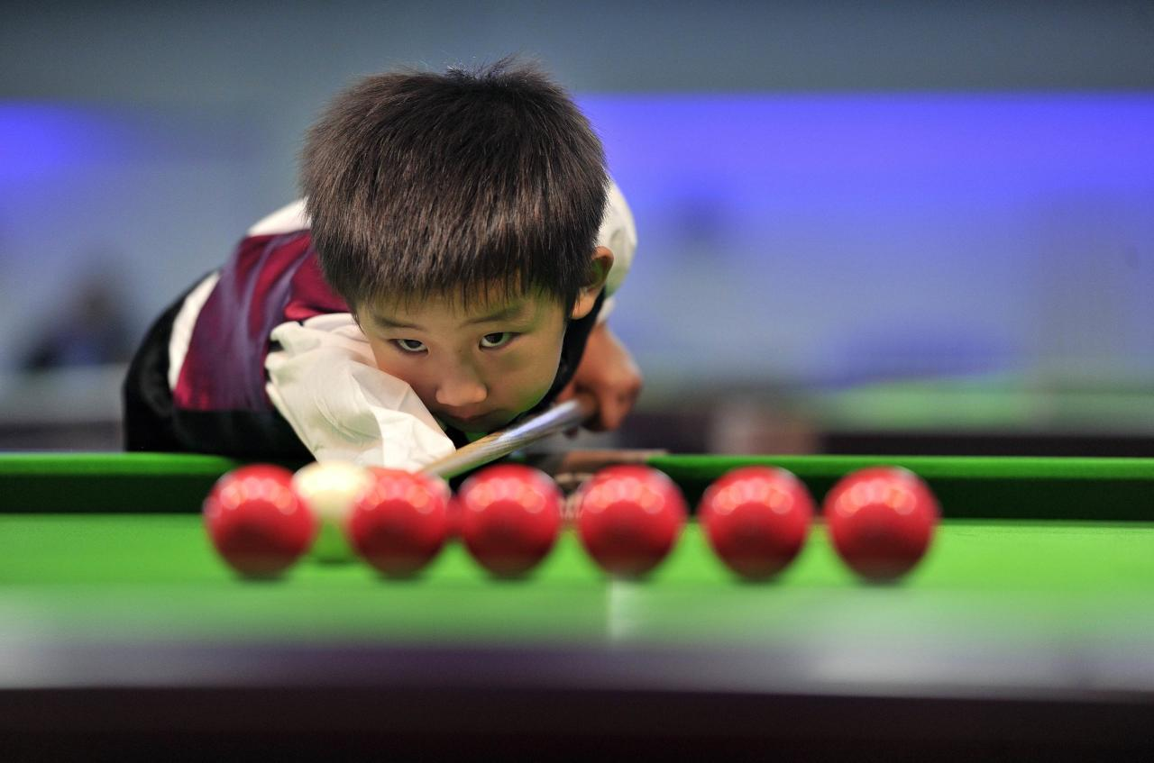 Three-year-old Wang Wuka practises before playing snooker with seven-time World Championship winner Stephen Hendry of Britain in Beijing September 22, 2013. Wuka's father Wang Yin, a snooker fan, has been teaching his son the sport for more than two years. The boy, who vows to be a top snooker player, undergoes five hours of training daily to shoot the balls with precision. Picture taken September 22, 2013. REUTERS/Stringer (CHINA - Tags: SPORT SOCIETY TPX IMAGES OF THE DAY) CHINA OUT. NO COMMERCIAL OR EDITORIAL SALES IN CHINA