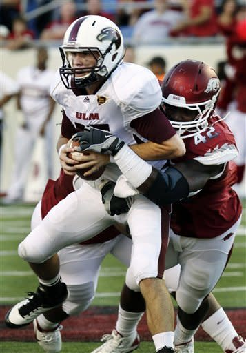 Louisiana Monroe quarterback Kolton Browning, left, is sacked by Arkansas defensive end Chris Smith (42) during the first quarter of an NCAA college football game in Little Rock, Ark., Saturday, Sept. 8, 2012. (AP Photo/Danny Johnston)