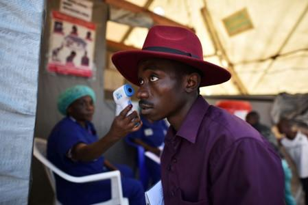 FILE PHOTO: A health worker checks the temperature of a man as part of the ebola screening upon entering the General Hospital in Goma