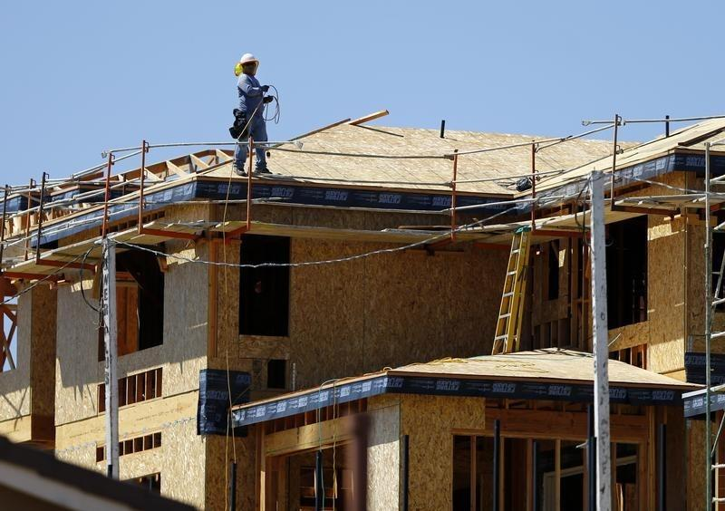 A worker walks on the roof of a new home under construction in Carlsbad