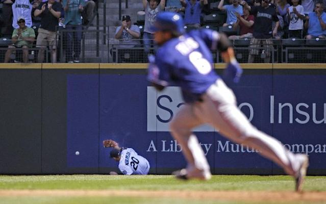 Texas Rangers' Tomas Telis, right, races toward second base on a three-run double as Seattle Mariners right fielder Logan Morrison (20) tumbles after chasing Telis' fly ball in the second inning of a baseball game Wednesday, Aug. 27, 2014, in Seattle. AP Photo/Elaine Thompson)