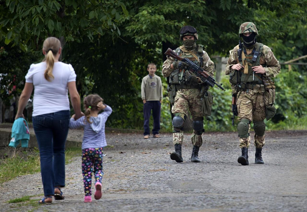 Ukrainian Government forces soldiers patrol the area at Bobovysche village near Mukacheve, Ukraine, Monday, July 13, 2015, after two people were killed Saturday in a Right Sector gun-and-grenade attack on police in a western Ukrainian city. Police surrounded gunmen on Saturday in a wooded area of Mukacheve and have been trying to negotiate their surrender since then. (AP Photo/Petro Zadorozhnyy)