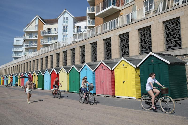Cyclists make their way past the beach huts on Boscombe beach, Dorset (PA)