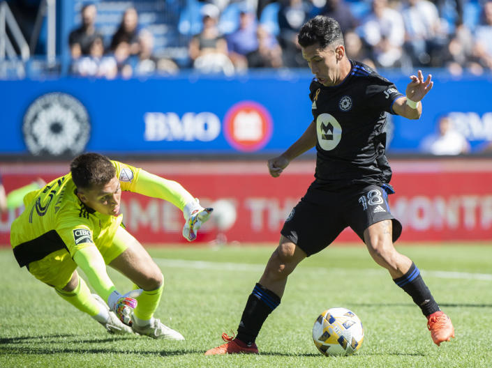 CF Montreal's Joaquin Torres, right, moves in on Chicago Fire FC goalkeeper Gabriel Slonina during first half MLS soccer action in Montreal, Sunday, Sept. 19, 2021. (Graham Hughes/The Canadian Press via AP)